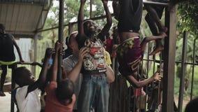 Kisumu, Kenya - 21 maggio 2018: Uomini caucasici divertendosi con i bambini in Africa Il bambino maschio della tenuta, aiutante l stock footage
