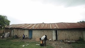 KISUMU KENYA - MAJ 15, 2018: Afrikansk familj nära deras hem Kvinnatvagningkläder i handfat i sommardag stock video