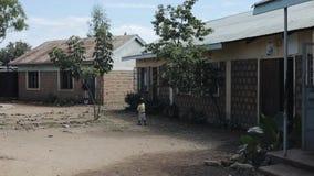 KISUMU KENYA - MAJ 15, 2018: Afrikansk familj nära deras hem Lite går pojken till och med en tom fattig by i sommar lager videofilmer