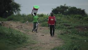 Kisumu Kenya - Maj 23, 2018: Den afrikanska kvinnan som går till och med landsvägen som bär bowlar på hennes huvud Mannen går när lager videofilmer