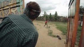 KISUMU KENYA - MAJ 15, 2018: Den Caucasian kvinnan plirar över staketet Afrikansk pojketonåring som rider en sparkcykel stock video