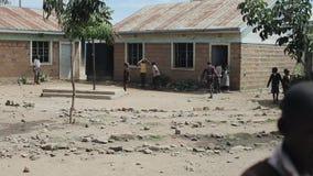 KISUMU KENYA - MAJ 15, 2018: Grupp av afrikanska barn i likformign som spelar fotboll i skolgården Fattig by in stock video