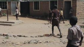 KISUMU KENYA - MAJ 15, 2018: Grupp av afrikanska barn i likformign som spelar fotboll utanför skolan tillsammans som tycker om lager videofilmer