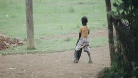 Kisumu Kenya - Maj 15, 2018: Sikt till och med blad av afrikanska pojkar som spelar med gummihjul på vägen Ungar som har gyckel t stock video