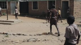 KISUMU,KENYA - MAY 15, 2018: Group of african children in uniform playing football outside the school together, enjoying stock video footage