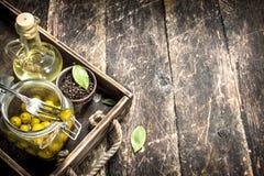 Kiszone oliwki z olejem i pikantność na starej tacy obrazy stock