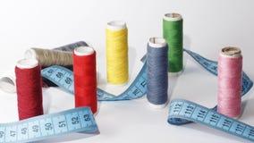 Kit de couture, aiguilles, fil et bande de mesure sur un fond blanc Photo stock