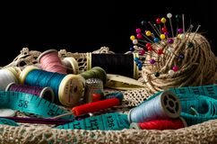 Kit de couture avec des bobines de fil et d'aiguilles sur le fond noir Photo stock