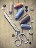 Kit de couture Ciseaux, bobines avec le fil et aiguilles sur le vieux fond en bois Photos libres de droits