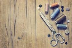 Kit de couture Ciseaux, bobines avec le fil et aiguilles sur le vieux fond en bois Images libres de droits