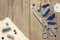 Kit de couture Ciseaux, bobines avec le fil et aiguilles sur le vieux fond en bois Photographie stock libre de droits