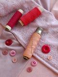Kit de couture dans le rose sur le fond de tissu Images stock