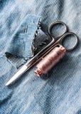 Kit de couture des fils, des ciseaux et d'aiguille sur le backround de jeans Photo libre de droits