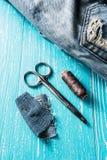 Kit de couture des fils, des ciseaux et d'aiguille sur le backround en bois de jeans Image libre de droits