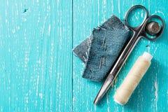 Kit de couture des fils, des ciseaux et d'aiguille sur le backround en bois de jeans Photos libres de droits