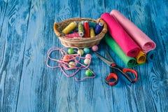 Kit de couture sur une table en bois Fil, aiguilles, ciseaux et a à Photo libre de droits
