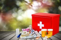 Kit de premiers secours avec des fournitures médicales sur la lumière Image stock