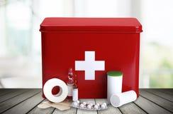 Kit de premiers secours avec des fournitures médicales sur la lumière Photographie stock libre de droits