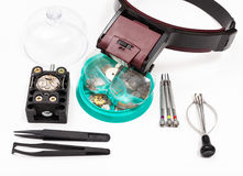Kit of tools with head-mounted magnifier. Watchmaker workshop - kit of tools with head-mounted magnifier and spare parts for repairing mechanical watch on white Stock Photos