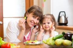 妇女和女儿烹调和获得乐趣在kitch 库存图片