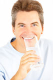 Kitchen. Handsome smiling man drinking water Stock Image