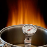 Kitchen. Cooking thermometer in the hot pot with fire in the background Stock Image