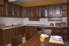 Kitchen. Brown wood kitchen with dining table royalty free stock photo