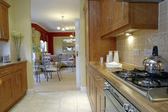 Kitchen. Interior in modern apartment with wood fittings looking to dining area Stock Photos