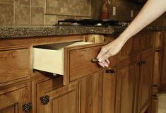 In the kitchen. Female opening (or closing) kitchen cabinet door Royalty Free Stock Photos