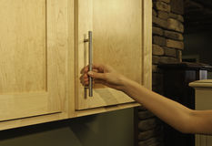 In the kitchen. Female opening (or closing) wood kitchen cabinet door Royalty Free Stock Photo