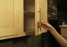 In the kitchen. Female opening (or closing) wood kitchen cabinet door Royalty Free Stock Images
