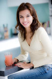 In The Kitchen. A young woman having juice in the kitchen stock photo