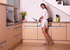 Kitchen. Young woman in kitchen preparing food royalty free stock photos