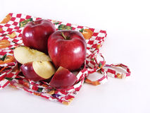 Kitchen Apples. Two whole apples and a partial sliced apple resting on a colorful kitchen apron. Over white, with room for text Stock Images