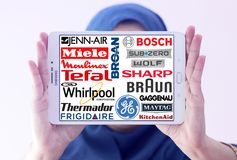 Kitchen appliance logos. Kitchen appliance companies on samsung tablet holded by arab muslim woman royalty free stock photo
