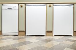 Kitchen appliances. A fitted kitchen with dishwasher,fridge and freezer in a row royalty free stock photos