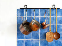 Kitchen appliances. Hanging retro design copper kitchenware set. Pots, stewpots, saucepans, coffee maker, kitchen spoon, skimmer hanging on. Blue tiles wall Stock Photography