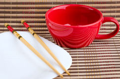 Kitchen appliances for sushi. Asian cup for tea and a white plate with bamboo sticks for sushi Stock Photo