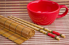 Kitchen appliances for sushi. Empty cup and sushi chopsticks on a bamboo napkin Stock Photo