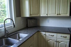 Kitchen Area. Showing the sink, tap, cupboards, and quartz countertop Stock Image