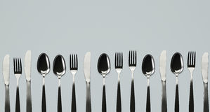 Knives, Forks and Spoons in a Row. Table knives, forks and spoons in a row. 3D illustration Royalty Free Illustration