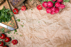 Kitchen background with baking paper, tomatoes, radish and parsley. Copy space Royalty Free Stock Images
