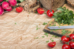 Kitchen background with baking paper, tomatoes, radish and parsley. Copy space Stock Photos