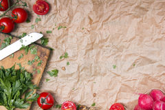 Kitchen background with baking paper, tomatoes, radish and parsley. Copy space Royalty Free Stock Photo