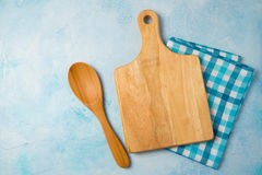 Kitchen background with cutting board, tablecloth and spoon over blue stone counter. Royalty Free Stock Photography