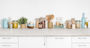 Kitchen bench interior with various herbs, spices, utensils on white royalty free stock image