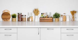 Kitchen bench shelf with various herbs, spices, utensils on white. Background royalty free stock photos