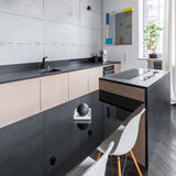Kitchen with black countertop. Modern and elegant kitchen with black countertop and table and white chairs stock photo