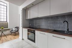Kitchen with black sink granite worktop. Modern kitchen with black sink and granite worktop, gray wall and big window stock photos