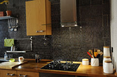 Kitchen with Black Tiles, Natural Wood Worktop, Stove royalty free stock photos